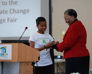 Tracy Hoxobes hands over a green thread to Hon. Minister Nandi-Ndaitwah